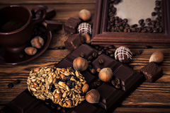 Roasted coffee beans, chocolate, candy, nuts, cup and the frame for inscriptions on the wooden background Stock Image