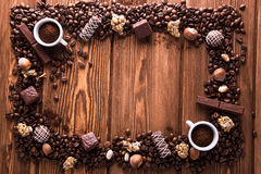 Roasted coffee beans, chocolate, candy, nuts, cup and the frame for inscriptions on wooden background Royalty Free Stock Photo