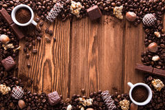 Roasted coffee beans, chocolate, candy, nuts, cup and the frame for inscriptions on wooden background Royalty Free Stock Photos