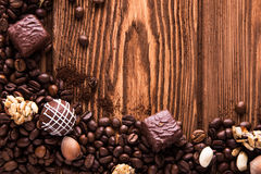 Roasted coffee beans, chocolate, candy, nuts  and the place for inscriptions on wooden background Royalty Free Stock Photography