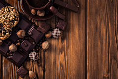 Roasted coffee beans, chocolate, muesli, candy, nuts and cup on the wooden background Stock Photography