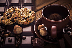 Roasted coffee beans, chocolate, muesli, candy, nuts and cup on the wooden background Stock Images