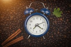 Roasted coffee beans, cinnamon sticks and alarm clock. Wake up. Good morning. Autumn mood. Background, close-up view. royalty free stock photo