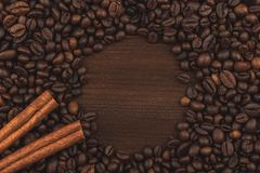 Roasted coffee beans and cinnamon sticks. Background, close-up view. royalty free stock photo