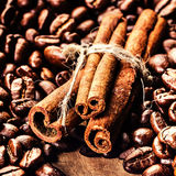 Roasted Coffee beans and cinnamon sticks on grunge wooden backgr Stock Images