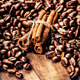 Roasted Coffee beans and cinnamon sticks on grunge wooden backgr Stock Image