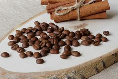 Roasted coffee beans and cinnamon sticks on a wooden stand and coarse jute canvas. stock images