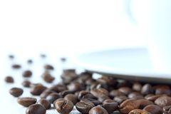 Real morning starts with natural coffee. Roasted coffee beans close-up on the background of blurred outlines of the cup royalty free stock images