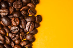 Roasted coffee beans close up. Yellow background. Space for text Royalty Free Stock Photography