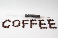 roasted coffee beans and coffee beans filled syringe on table Royalty Free Stock Photo