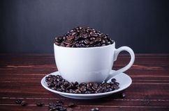 Roasted coffee beans in coffee cup. On wooden background Stock Images