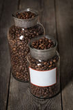 Roasted coffee beans in a cristal jar on wood background Royalty Free Stock Photography