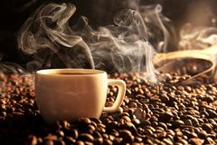 Roasted coffee beans with cup. On dark background Royalty Free Stock Image