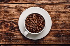 Roasted coffee beans in cup. Over wooden surface royalty free stock photography