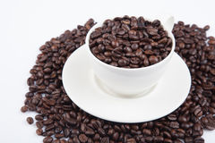 Roasted coffee beans with a cup Royalty Free Stock Photos