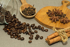 Roasted coffee beans and different spices. Roasted coffee beans in glass jar and some spices - cinnamon, clove and anise prepared for cooking stock photo