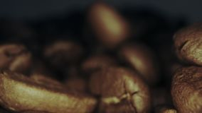 Roasted coffee beans fall near camera, extreme close-up dolly shot. Macro dolly shot of roasted coffee beans stock video