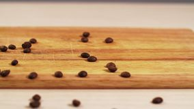 Roasted coffee beans fall on the table close-up and scatter on the 4K board. Clear place for your isolated text pattern. Empty space for your title copy space stock footage