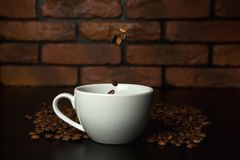 Roasted coffee beans falling into cup. Stock Photography