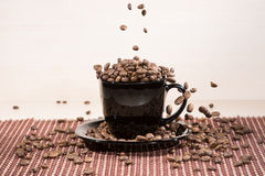 Roasted coffee beans falling down into black cup standing on black plate standing on tablemat. Stock Image
