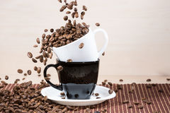 Roasted coffee beans falling down into white cup standing on a b Royalty Free Stock Image