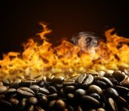 Roasted coffee beans with fire. Royalty Free Stock Photos