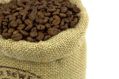 Roasted coffee beans in a flax bag. On white background Stock Photo