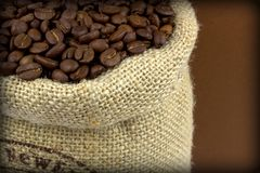 Roasted coffee beans in a flax bag. On brown background Royalty Free Stock Images