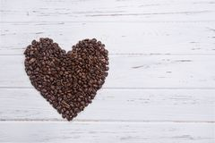 Roasted coffee beans in form of a heart on white wooden backgrou. Nd Royalty Free Stock Photos