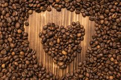 Roasted coffee beans in the form of heart wooden background stock photography