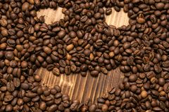 Roasted coffee beans in the form of a smiling face on a wooden background royalty free stock image