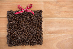 Roasted coffee beans forming gift box. On wooden background Royalty Free Stock Image