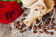 Roasted coffee beans, fresh red rose, coarse burlap sac on old wooden table. Vintage still life. Place for text. Top Stock Image