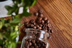Roasted coffee beans get out of overturned glass jar on homespun tablecloth, selective focus, side view. Side view of natural roasted coffee beans get out of Royalty Free Stock Photography