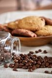 Roasted coffee beans get out of overturned glass jar on homespun tablecloth, selective focus, side view. Side view of natural roasted coffee beans get out of Royalty Free Stock Images