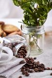 Roasted coffee beans get out of overturned glass jar on homespun tablecloth, selective focus, side view. Side view of natural roasted coffee beans get out of Stock Photo
