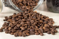 Roasted coffee beans get out of an overturned and open glass jar Royalty Free Stock Images