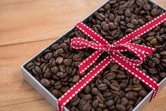 Roasted coffee beans in gift box. On wooden background Royalty Free Stock Image