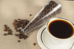 Roasted coffee beans in a glass bottle and a Cup of coffee on linen cloth Royalty Free Stock Image
