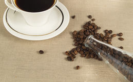 Roasted coffee beans in a glass bottle and a Cup of coffee on linen cloth Royalty Free Stock Photo