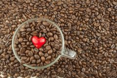 Roasted coffee beans in a glass cup. Love of coffee. We love coffee Royalty Free Stock Photo