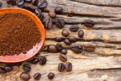 Roasted coffee beans and ground coffee in wooden spoon Stock Images