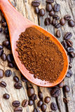 Roasted coffee beans and ground coffee in wooden spoon Stock Image