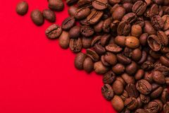 Roasted coffee beans on red background. Color surge trend. Roasted coffee beans isolated on red background. Color surge trend. Macro stock photography