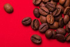 Roasted coffee beans on red background. Color surge trend. Roasted coffee beans isolated on red background. Color surge trend. Macro royalty free stock images