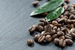 Roasted coffee beans and leaves on a dark background Stock Photography