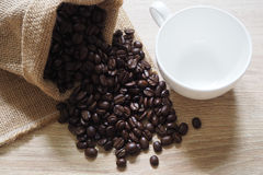 The roasted coffee beans in linen bag on the table and have empty coffee cups. For text input Royalty Free Stock Photos