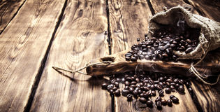 Roasted coffee beans in an old bag. On wooden background Stock Images