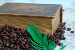 Roasted coffee beans, old book and a green pen Stock Photo