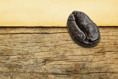 Roasted coffee beans on old paper on the wood background Stock Photography